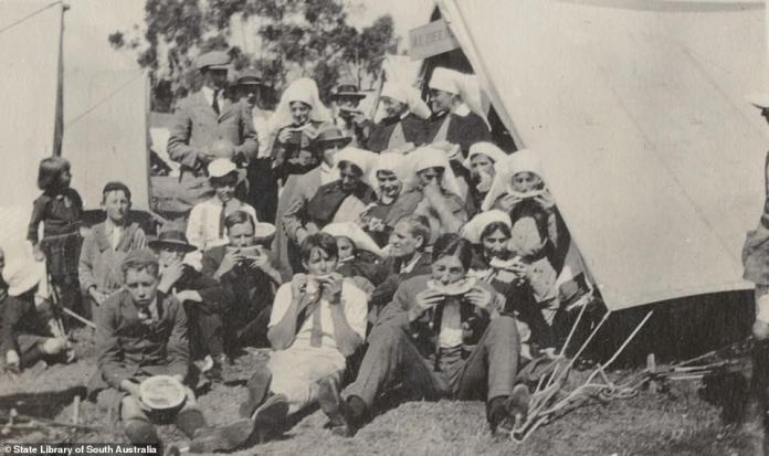 A group of men and women, including nurses, eating melon at the Jubilee Oval quarantine camp in 1919. Fresh fruit and supplies was supplied by outsiders through to the Post Office on site