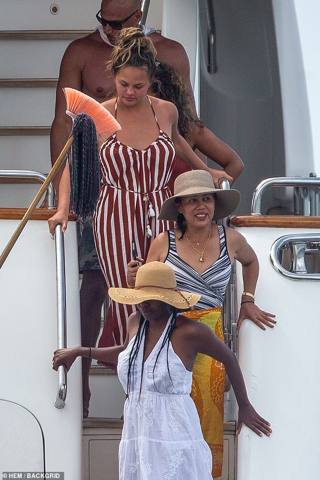 Fun on the high seas: the 5'9 '' star was chic when she wore a bra and swimsuit in a brown and white striped jumpsuit that had a V-neck, thin straps and a belt with white pompoms.  Teigen chose to roll the hems