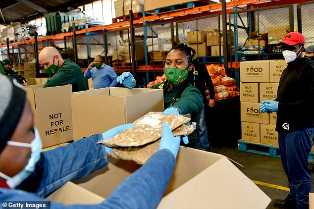 Mass unemployment, disruption to food production and declining aid as a result of the pandemic could push up an estimated 121 million people to the brink of starvation by the end of the year. Above,Springbok Women's Sevens captain Zintle Mpupha works to hand out food at a food bank in Cape Town, South Africa