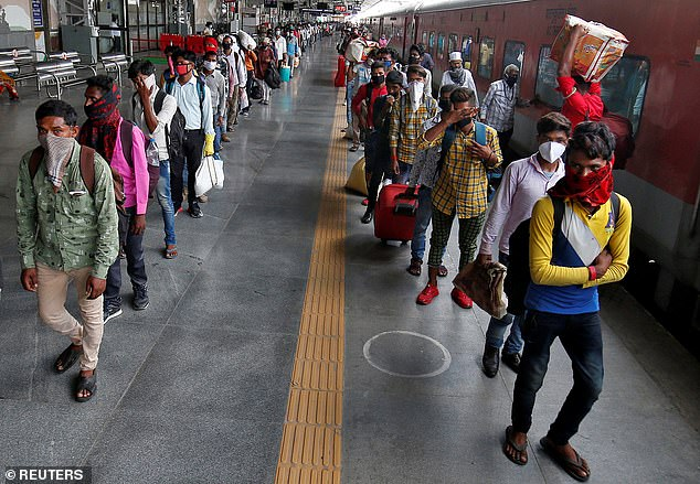 In India, travel restrictions meant that millions of migrant workers were unable to work on farms, leaving farmers with no choice but to let their crops rot. Above, migrant workers and their families in India, who had left cities during lockdown, walk at a platform after they returned from their home state of Uttar Pradesh