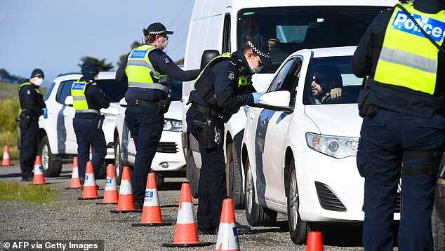 Police consult drivers on the outskirts of Melbourne on Thursday on the first day of the city's secondary lockdown