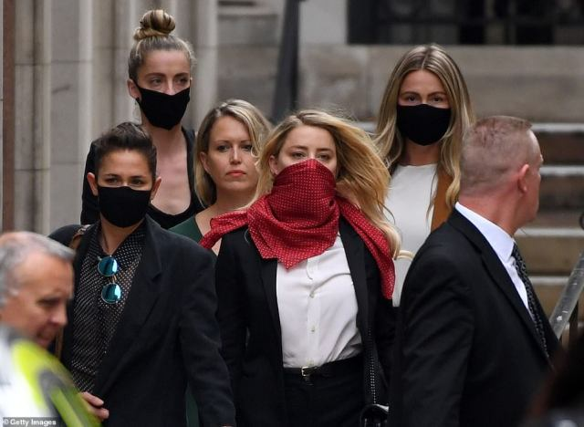 Heard leaving the High Court in London with 'Team Heard', including her girlfriendBianca Butti (front left)