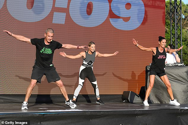 Keeping fit: Michelle performed the workouts alongside others on a stage which were then copied by hundreds in the park