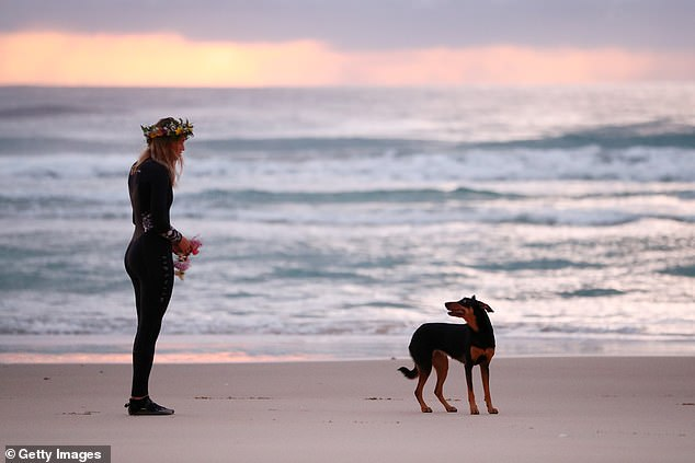 Ms Vlug and the couple's dog Rummi (pictured) are seen at the beach during the morning service