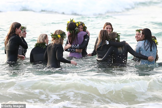 Ms Vlug and a handful of friends (pictured on Saturday morning) waded into the same waters that took her beloved boyfriend to share an emotional farewell