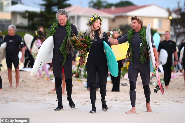 Ms Vlug (pictured, centre) and Pullin's father (left) carry their boards out to the surf during the morning service