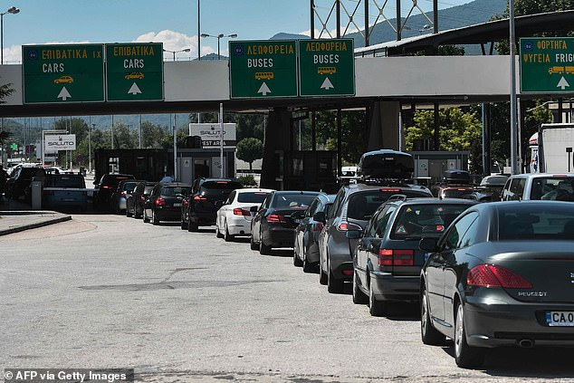 """Cars wait in line as they queue at the Greek-Bulgarian border crossing in Promachonas on July 10, 2020. - Greek authorities on July 9, 2020 expressed concern over the increase in Covid-19 cases in the neighboring Balkans, highlighting the risk of """"imported cases"""" due to the arrival in Greece of tourists over land borders"""