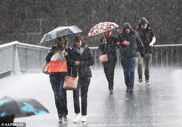 Heavy rainfall and wild winds could rip out trees and powerlines in parts of the country as residents are warned to brace for flash flooding (pictured, rain in Melbourne)