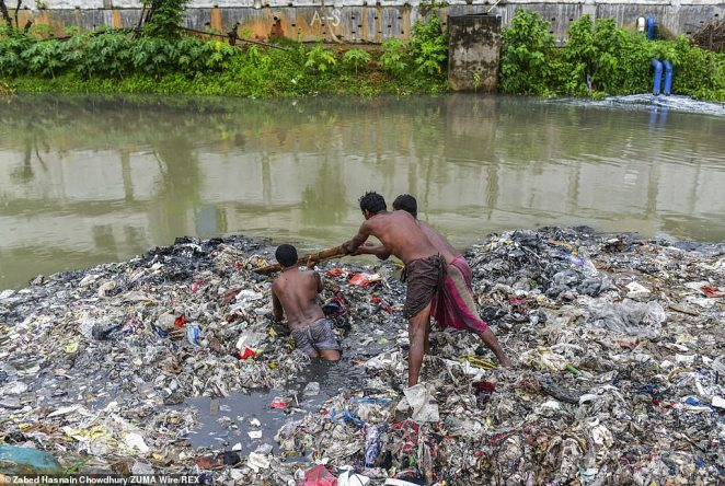 The volunteers attempt to separate the island of waste with a bamboo pole as they clean the river bank without wearing protection