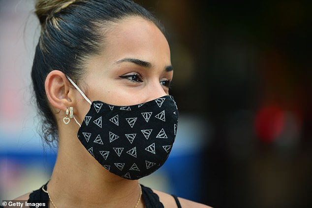Experts are divided as to whether coronavirus can be spread through floating droplets in the air, though the World Health Organization acknowledged this was possible. The above image shows a woman wearing a face mask in Miami Beach, Florida, on July 6