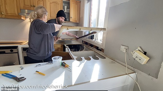 DURING:'I smashed out the old tiles, replaced the gyprock, plastered, tiled, replaced the bench tops and cut the stone, painted the cupboards and installed new handles,' Nicole said