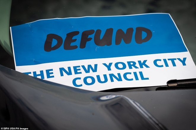 A sign calls for the defunding of the New York City Councilduring a Blue Lives Matter rally in Bay Ridge, Brooklyn, on Saturday