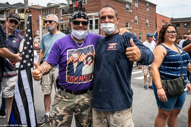 A man wearing a t-shirt that denounces Democratic Senator Charles Schumer and House Speaker Nancy Pelosi as 'commies' is seen embracing a friendduring a Blue Lives Matter rally in Bay Ridge, Brooklyn, on Saturday