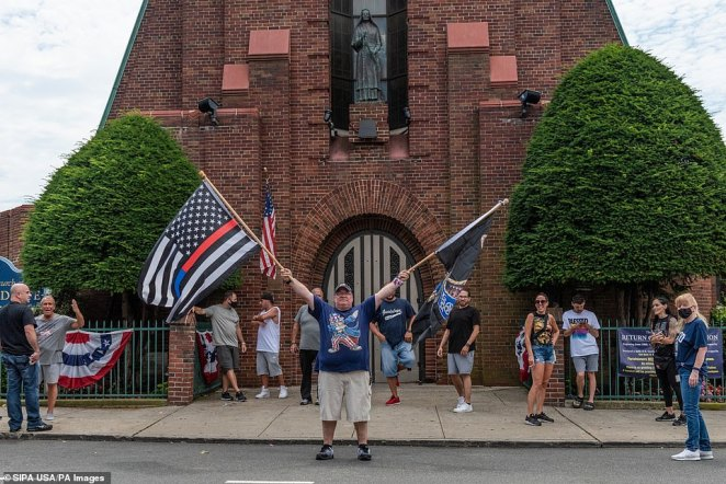 A pro-police demonstrator is seen above holding two flagsduring a Blue Lives Matter rally in Bay Ridge, Brooklyn, on Saturday