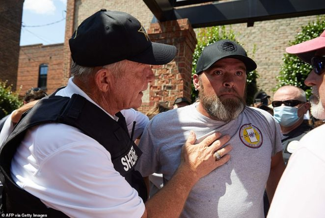 Alamance County Sheriff, Terry Johnson calms Gary Williamson, founder of Taking Back Alamance County, a neo-Confederate group, after supporters from the Burlington-Alamance March For Justice and Community rang the bell outside the courthouse in Graham, North Carolina, on Saturday