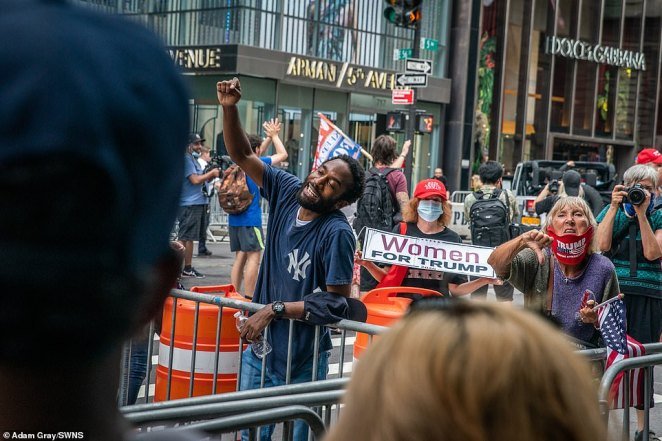 Supporters of President Trump give a thumbs down to opponents during a demonstration in front of Trump Tower in New York City on Saturday
