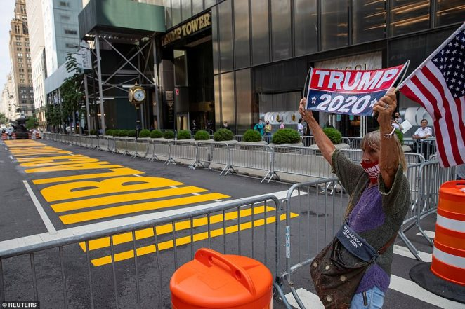 A Trump supporter holds a 'Trump 2020' sign and an American flagduring a demonstration in front of Trump Tower in New York City on Saturday