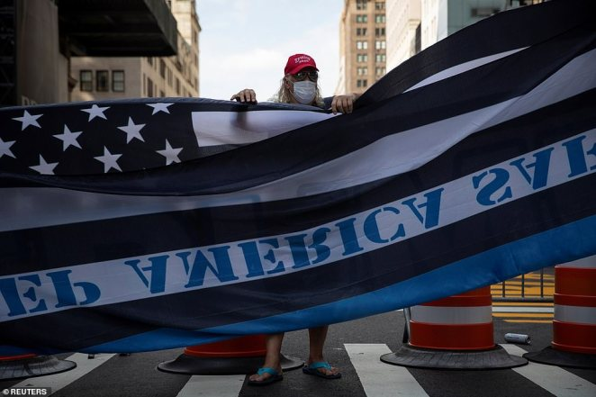 A Trump supporters stands behind the flagduring a demonstration in front of Trump Tower in New York City on Saturday