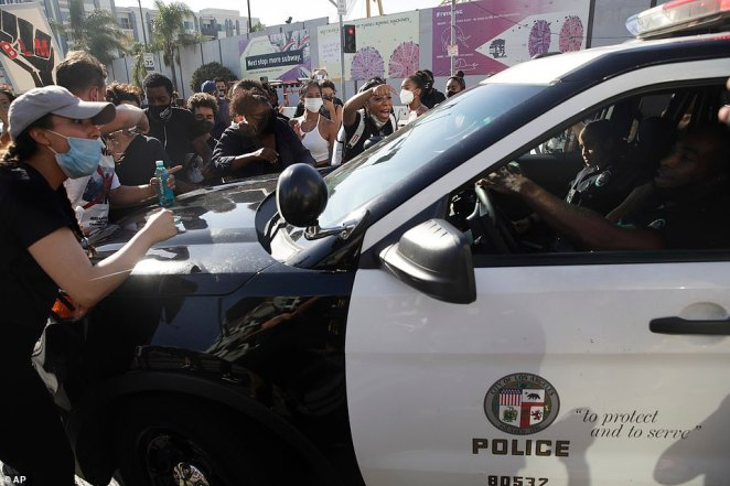 Demonstrators block a police vehicle with two officers inside during a protest in memory of Breonna Taylor in Los Angeles on Saturday