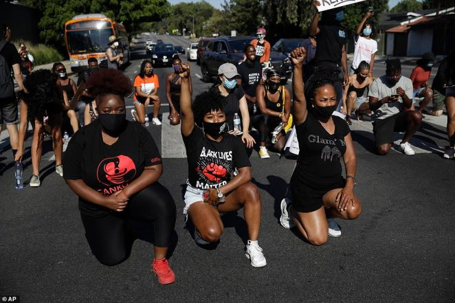 Demonstrators take a knee during a protest in memory of Breonna Taylor in Los Angeles on Saturday