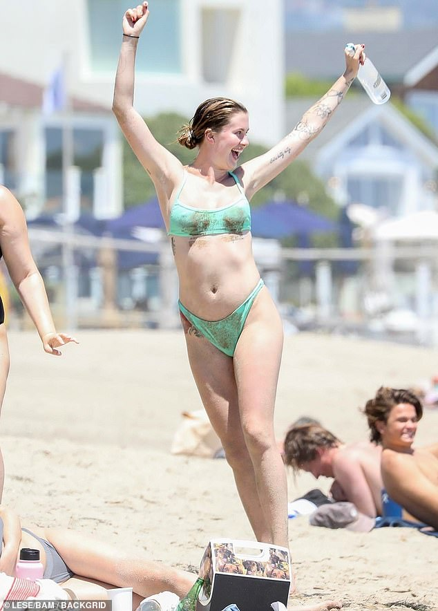 Having a ball: Ireland Baldwin was seen frolicking on the beach this weekend with her boyfriend Corey Harper and some pals