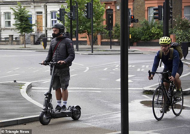 A bicycle arrives behind an electric scooter as they both cross a junction in south west London