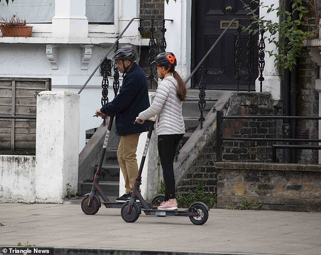 Two people in helmets ride their electric scooters side by side on the sidewalk