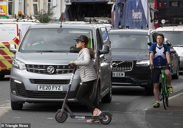 Electric scooter driver crosses busy road as cars stop at railway crossing on Friday