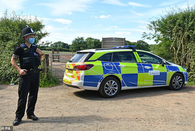 A police officer wearing a face mask stands by his car outside the gates of Rook Row Farm near Malvern