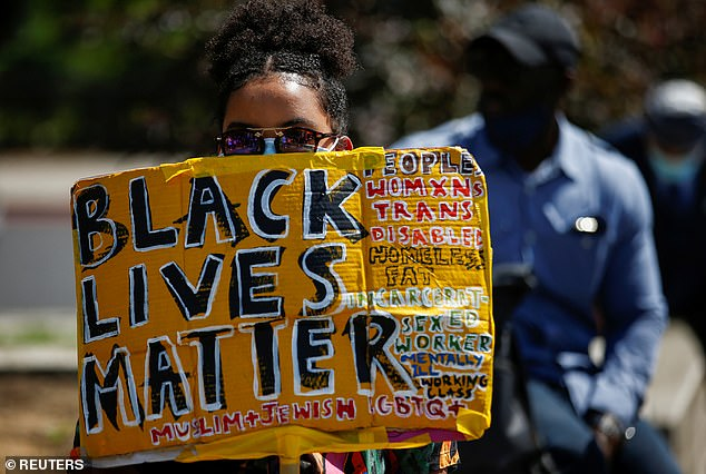 A demonstrator holds a placard during a Black Lives Matter protest at Marble Arch, in London, July 12