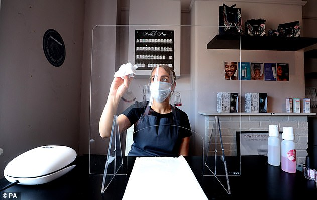 Roberta Dyer, owner of Roberta Beauty Redefined in Knutsford, sits behind a protective screen at her salon yesterday as it prepares to open its doors after months in lockdown