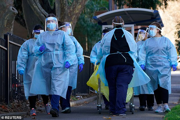 Health workers take tests into a sealed off public housing tower in Melbourne on July 8. Residents were unable to leave during the hard lockdown which has now ended for most