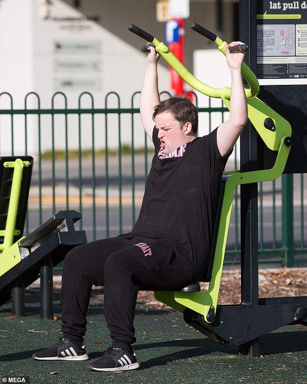 Working hard: Channelling his inner Arnold Schwarzenegger, Kieran was seen gritting his teeth as he performed lateral pull-downs on an exercise machine