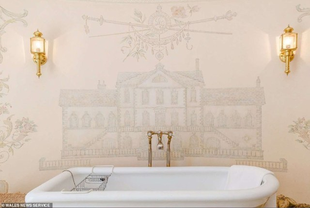 One of the 18th-century Welsh manor house's bathrooms features a mural of the house behind the roll-top bath