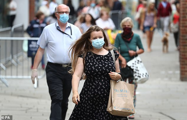 A woman wears a face covering whilst shopping in Canterbury, Kent, before the announcement that it will soon be mandatory to wear a face covering in shops in England