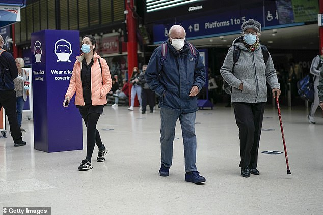 People wear face masks at the train station in Liverpool on Tuesday. They are set to become mandatory in shops