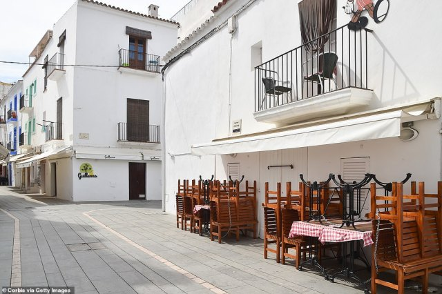 View of empty street and closed restaurant in Ibiza, Spain. Chairs and tabled remain turned over amid a lack of tourists to the area