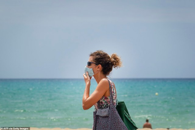 A woman adjusts her mask at Palma Beach in Palma de Mallorca