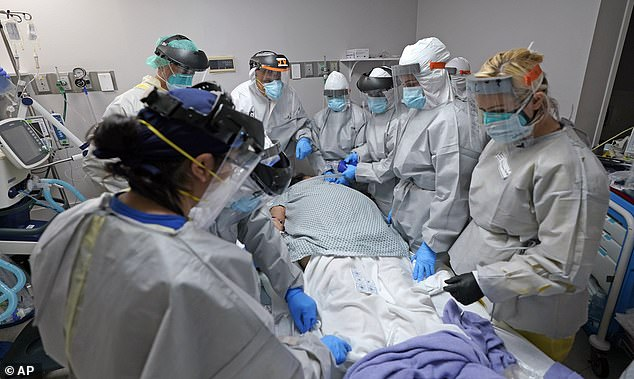 Dr. Joseph Varon, top with JV on shield, leads a team as they tried without success to save the life of a patient inside the Coronavirus Unit at United Memorial Medical Center, Monday, July 6