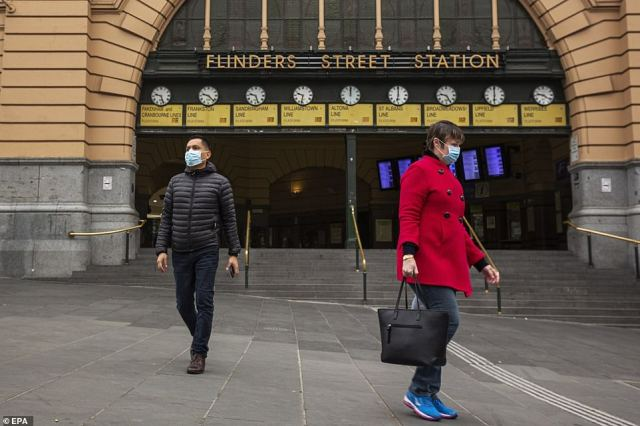 People wear masks outside Flinders Street Station in Melbourne as the city endures a six-week lockdown to slow the spread of the deadly virus