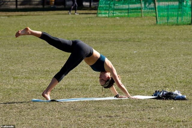 A cold front is slowly sinking in, meaning patchy rain at times, despite the highs, before a drop in temperatures into next week. Pictured: A woman doing yoga on Clapham Common