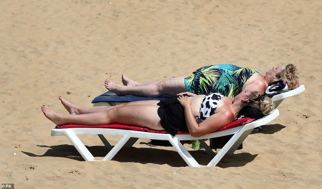 Two people lie back on the deck chairs and soak up the sun on the beach in Margate, Kent, as mercury levels rise in the UK