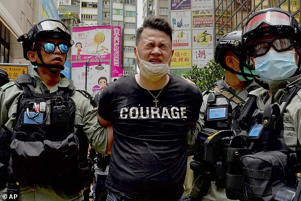 Police detain a protester after spraying pepper spray during a protest marking the 23rd anniversary of UK pulling out of Hong Kong in 1997