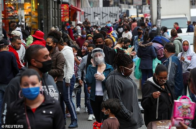A woman in a face shield talks on the phone as people walk at a popular shopping street amid the outbreak of coronavirus in Sao Paulo, Brazil
