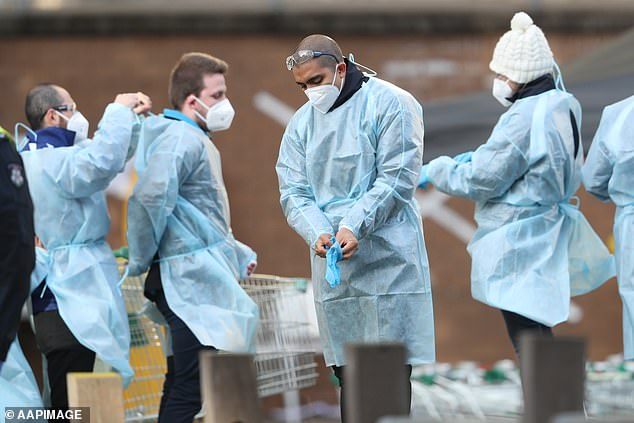 Medical workers are seen at a Government Commission tower in North Melbourne which remains under strict lockdown