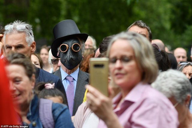 The protestor wearing a plague doctor-style masks is seen through the crowd as he listens to speakers during the rally