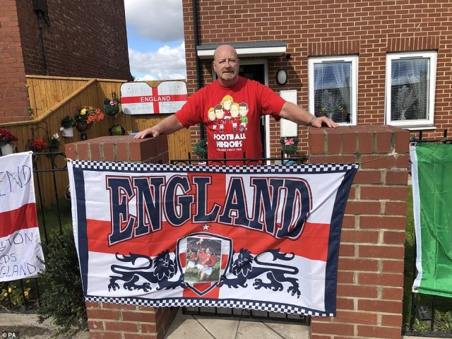 Peter Cowans, 64, with the display of flags outside his home in Ashington, ahead of Jack Charlton's funeral procession today