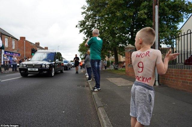 A young boy, Mason King, six, pays tribute to Jack Charlton as the funeral cortege passes through Ashington today