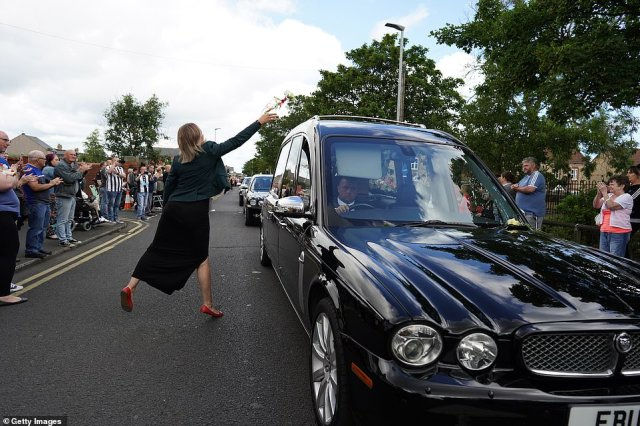 A woman throws a tribute over the hearse as people line the streets to pay tribute to Jack Charlton this morning