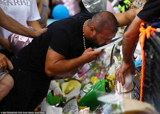 One unidentified relative was seen kissing a framed photo of one of the victims left at the makeshift memorial